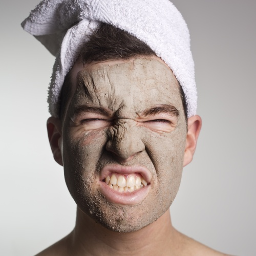 man with a green mud mask on this face,man with expresive face,