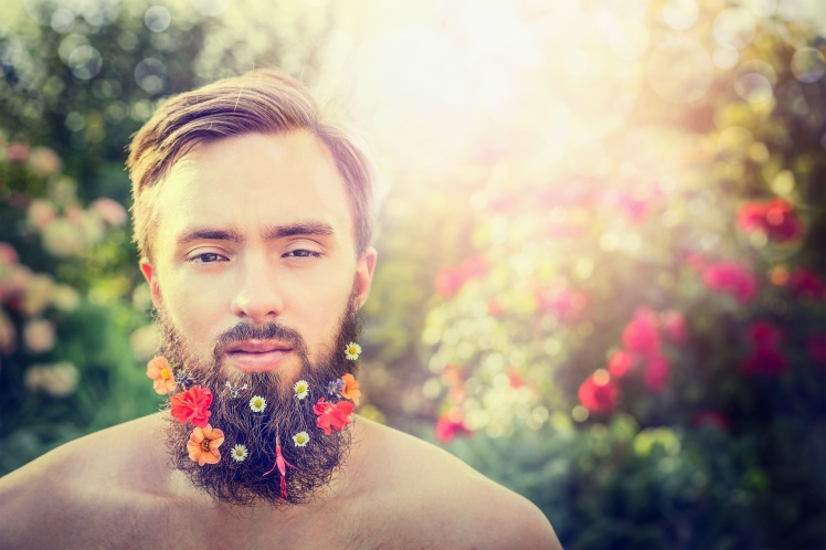 stylish man's face with a beard with flowers in his beard on natural bright-colored background