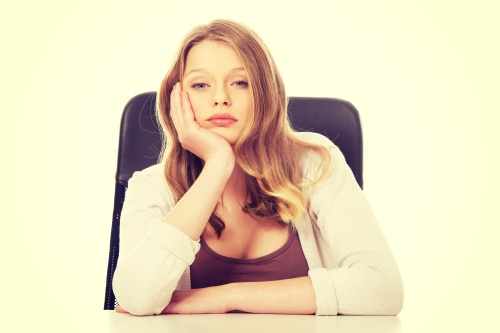Worried teenage woman sitting at the desk