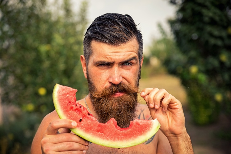 Happy brutal bearded man in the garden with juicy ripe watermelon