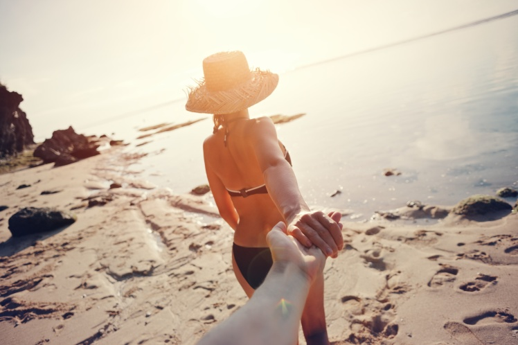Beautiful woman leading man through the sand beach at sunrise